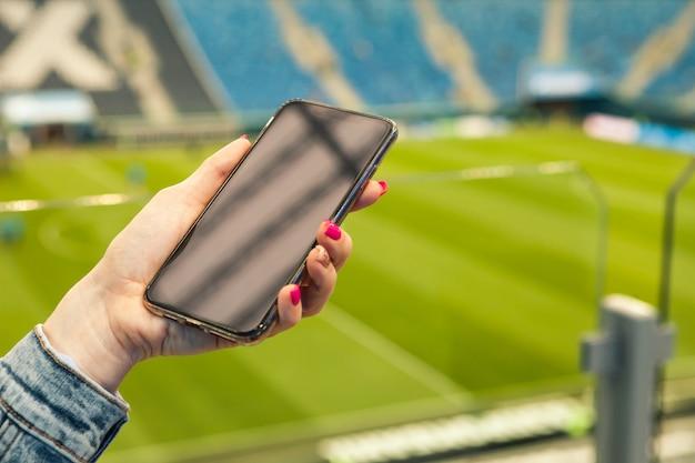 Una ragazza con il manicure rosa tiene uno smartphone in mano sullo sfondo di un campo di calcio.