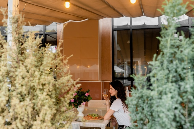 Ragazza con pinsa romana nella caffetteria sulla terrazza estiva. giovane donna che mangia pinsa e beve vino.