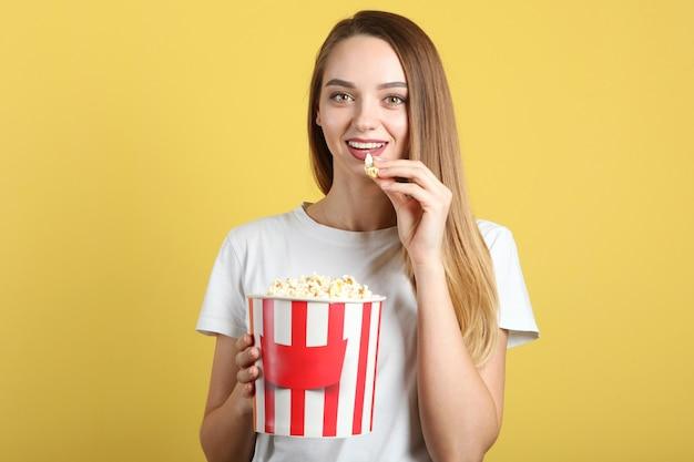 Ragazza con popcorn su sfondo colorato guarda un film d film