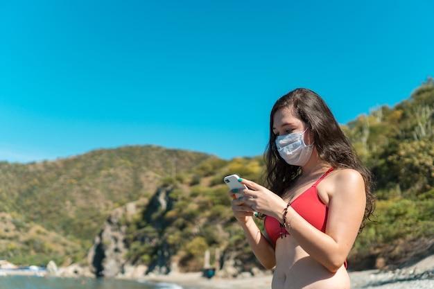 Ragazza con maschera protettiva e telefono in costume da bagno