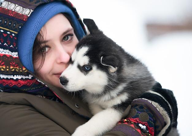 Ragazza con husky cucciolo su sfondo invernale