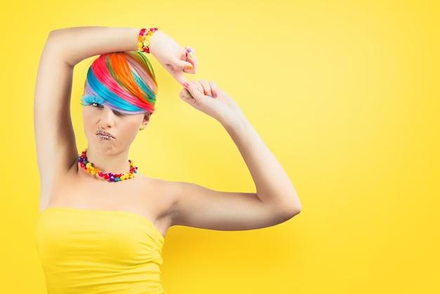 Ragazza con il trucco di moda colorato arcobaleno su sfondo giallo.