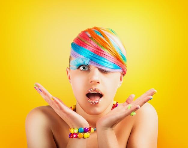 Ragazza con il trucco di moda colorato arcobaleno su giallo