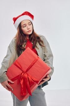 Ragazza con scatola regalo rossa vestiti di capodanno studio emozioni natale