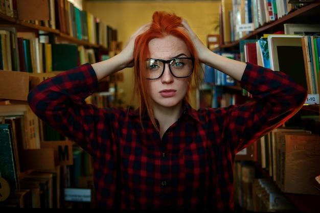 Una ragazza con i capelli rossi è in piedi in biblioteca, con gli occhiali