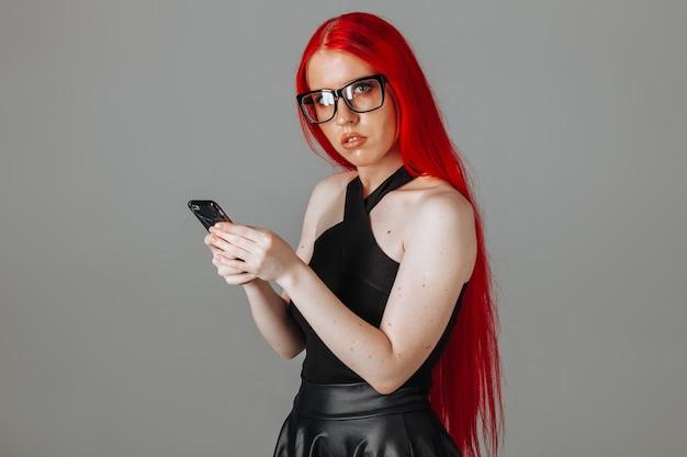 Ragazza con i capelli rossi con gli occhiali e una gonna di pelle scrive un messaggio al telefono