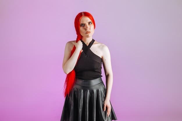 Ragazza con capelli lunghi rossi e gonna di pelle in posa su sfondo rosa