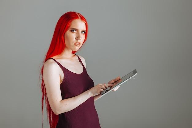 Ragazza con i capelli lunghi rossi che guarda un tablet