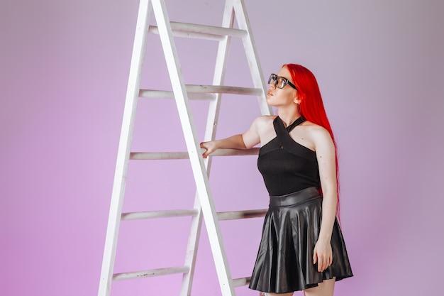 La ragazza con i capelli lunghi rossi con gli occhiali e una gonna di pelle sale una scala su uno sfondo rosa