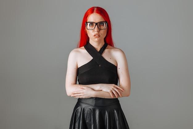 Ragazza con i capelli lunghi rossi con gli occhiali e una gonna di pelle in posa su uno sfondo grigio