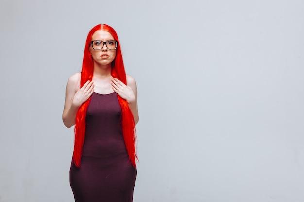 Ragazza con i capelli lunghi rossi con gli occhiali su uno sfondo grigio chiaro