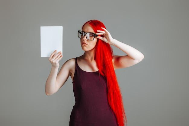 Ragazza con i capelli lunghi rossi con gli occhiali con un libro bianco