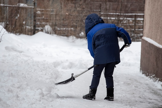 La ragazza con una pala pulisce la neve nel cortile. foto di alta qualità