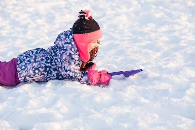 La ragazza con la pala giaceva sulla neve