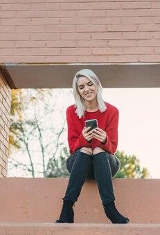 Ragazza con i capelli d'argento che si siede e naviga con il suo telefono. vestito con un maglione rosso.