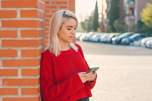 Ragazza con i capelli d'argento che scrive un messaggio con il suo telefono. appoggiato a una colonna della città.