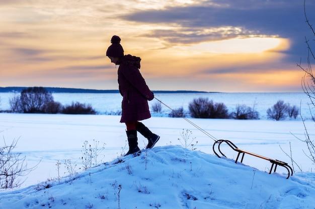 Ragazza con le slitte che scalano una collina, sera d'inverno, tramonto, stile di vita sano