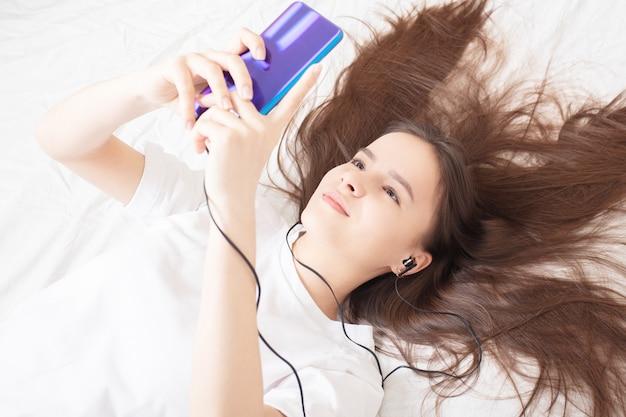 Una ragazza con uno smartphone a letto sorride, fa selfie, ascolta musica, gioca