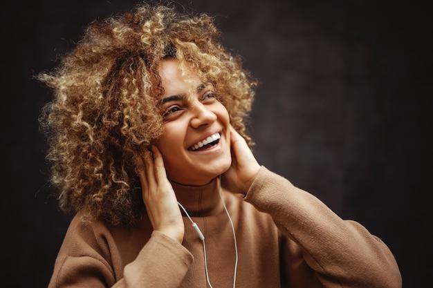 Ragazza con un sorriso sul viso tenendosi per mano sulle orecchie e godersi la musica