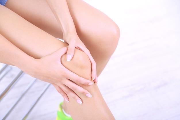 Ragazza con piede dolorante su superficie grigia