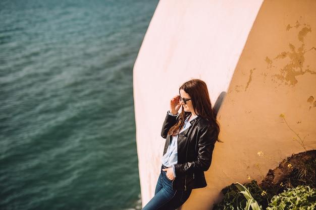 La ragazza con gli occhiali da sole riposa contro il muro giallo vicino al mare.