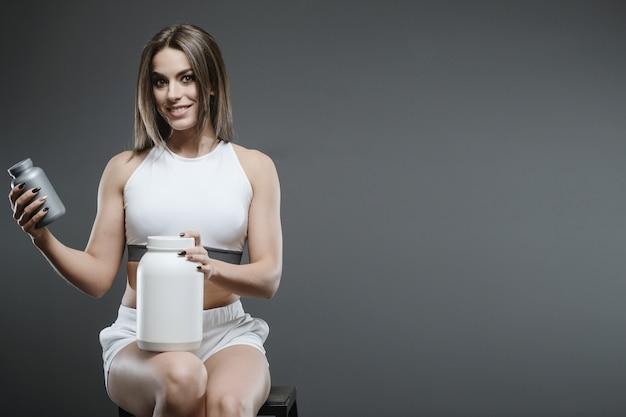 Ragazza con integratore di siero di latte in polvere