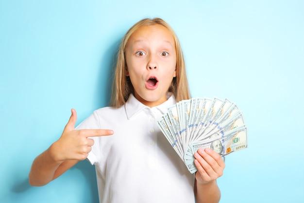 Ragazza con emozione a sorpresa che tiene i soldi in mano su sfondo blu