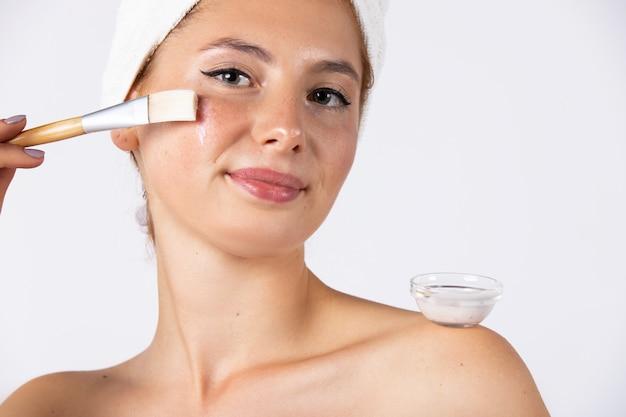 Una ragazza con un dolce sorriso e un asciugamano in testa, applica una maschera gel con un pennello. modello femminile alla moda con un bell'aspetto. foto su una parete bianca. foto di alta qualità