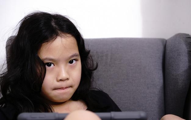 Ragazza con tablet guarda la fotocamera con perché mi spia l'umore con spazio di copia