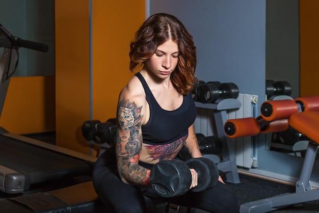 La ragazza con i tatuaggi sul fitness solleva i manubri