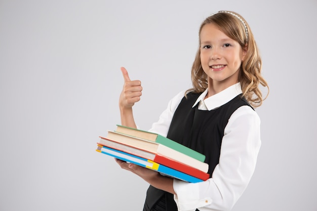 La ragazza con i libri di testo mostra un segno di classe.