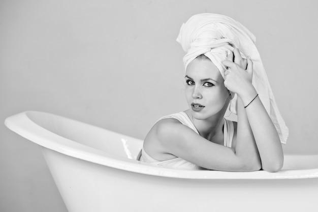 Ragazza con turbante asciugamano seduto nella vasca da bagno bianca. nero bianco.