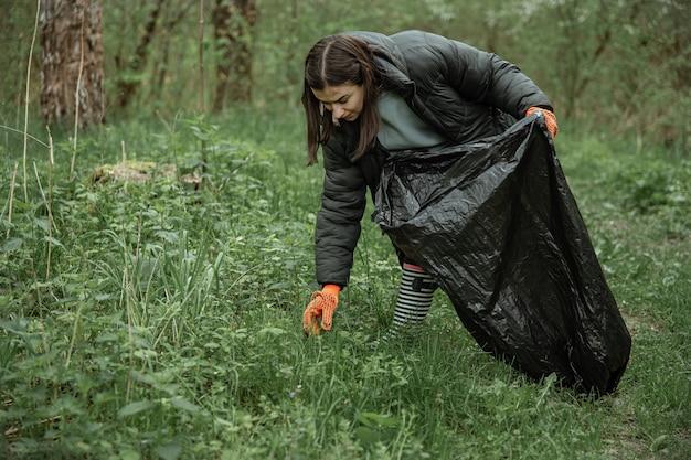 Una ragazza con un sacco della spazzatura pulisce l'ambiente dallo spazio della copia della spazzatura.