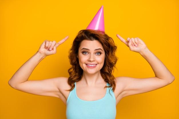 Ragazza con acconciatura alla moda e cappello da festa isolato sull'arancio