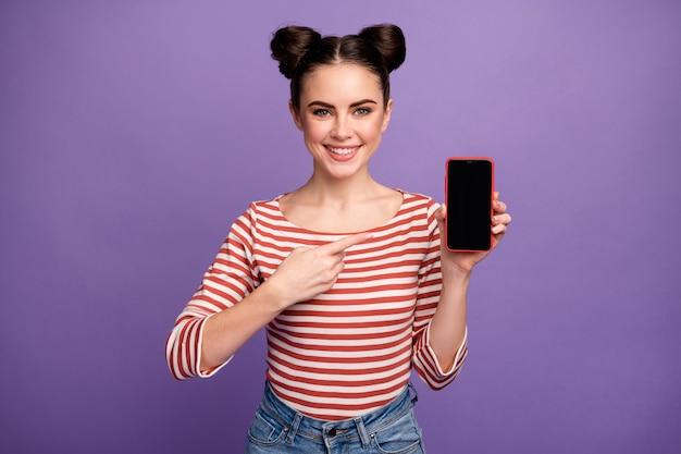 Ragazza con acconciatura alla moda che indica telefono