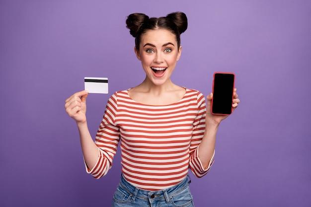 Ragazza con acconciatura alla moda tramite telefono e carta di credito
