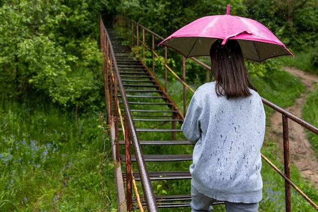 Una ragazza con un ombrello cammina nei boschi sotto la pioggia