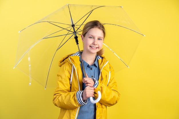 Ragazza con ombrello e impermeabile giallo sulla parete gialla