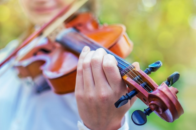 Ragazza con un violino su uno sfocato luminoso dal bokeh