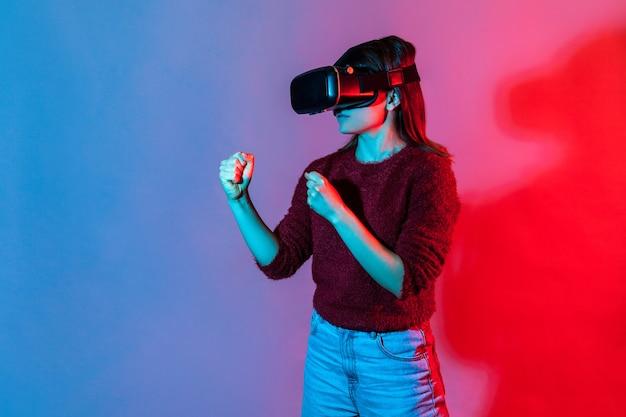 Ragazza con occhiali per realtà virtuale sulla testa che gioca a un gioco di combattimento, pugni chiusi pronti per la boxe.