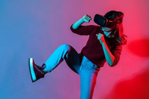Ragazza con occhiali per realtà virtuale che gioca al simulatore di gioco, alzando le gambe combattendo o superando ostacoli