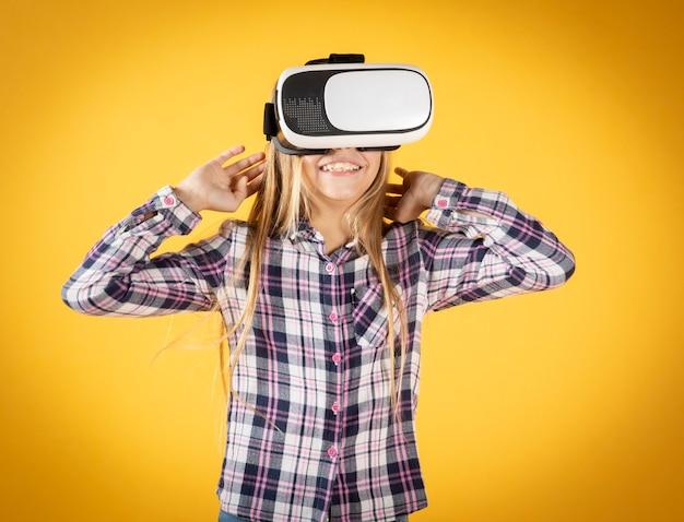 Ragazza con occhiali per realtà virtuale su una parete gialla