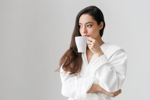 Ragazza con tazza bianca in mano. ritratto casuale della donna con la casa di indors femminile del caffè della bevanda o del tè. colpo dello studio.