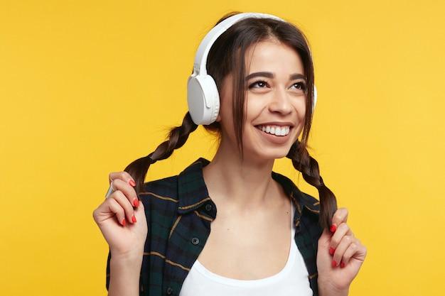 La ragazza con le cuffie bianche ascolta musica e gioca con le sue code di cavallo