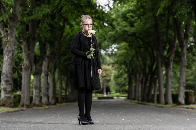 La ragazza con la rosa bianca in lutto è morta nel cimitero