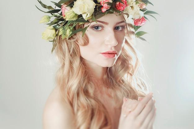 Ragazza con una corona di fiori in testa su sfondo bianco