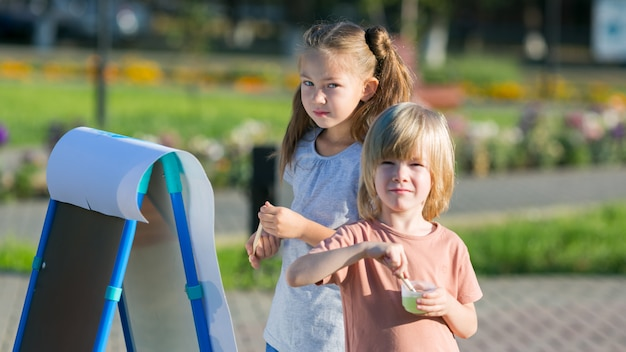 La ragazza con un fratello minore disegna le pitture sul parco di carta della città