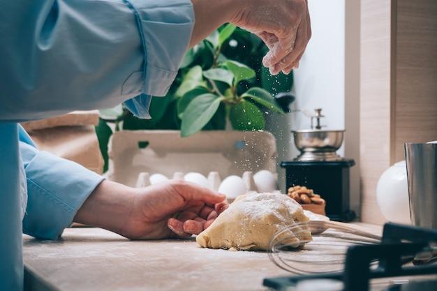 Una ragazza senza volto prepara l'impasto, lo cosparge di farina, primo piano. cucinare torte fatte in casa in cucina, a casa. sfondo culinario.