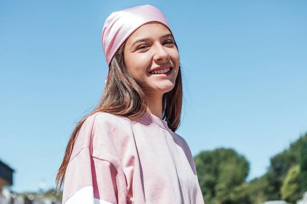 Donna ragazza con sciarpa testa rosa in testa, sorridente. giornata internazionale del cancro al seno, con il cielo sullo sfondo.