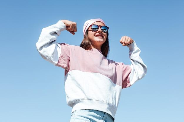 Ragazza donna con occhiali da sole e sciarpa rosa sulla testa, stringe il braccio in segno di forza. giornata internazionale del cancro al seno, con il cielo come sfondo.